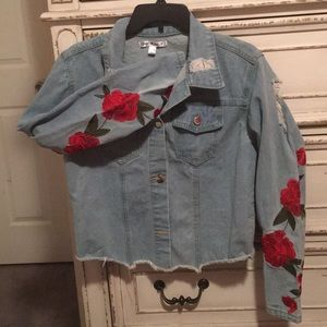 Distressed Jean jacket with rose details.